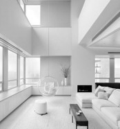 a pure white minimalist living room with a built-in fireplace, windows, white and black furniture