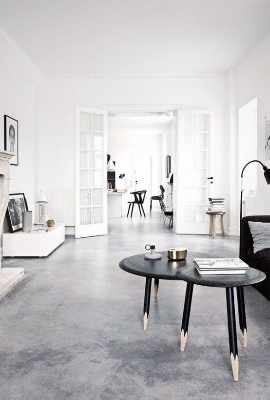 a minimalist meets Nordic living room with a black sofa and coffee tables, white and wooden furniture and a fireplace
