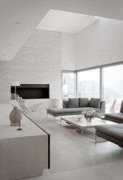 a neutral minimalist living room with a fireplace, grey furniture and a gorgeous view through the windows