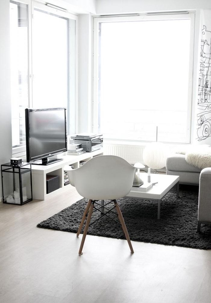 a minimalist monochromatic living room with laconic white furniture, panoramic windows, a fluffy rug and a printed statement wall