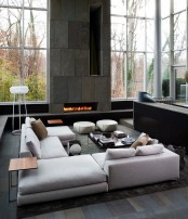 a minimalist living room with a large white sectional sofa, a stone clad fireplace wall, double-height ceilings, a conversation pit