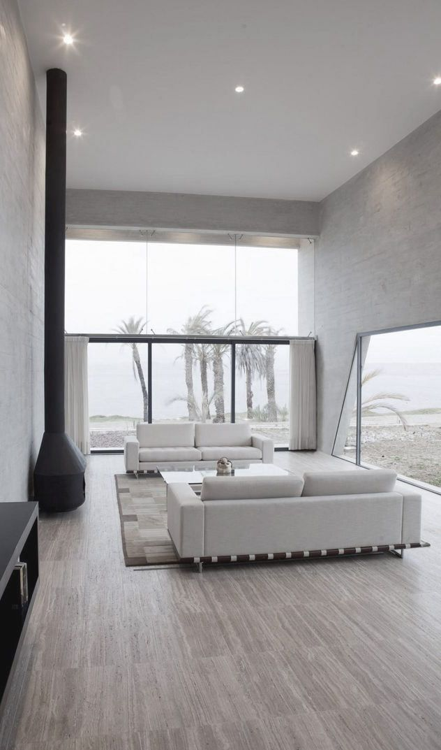 a minimalist neutral living room with oversized windows to fill the space with light, a hearth and two white sofas