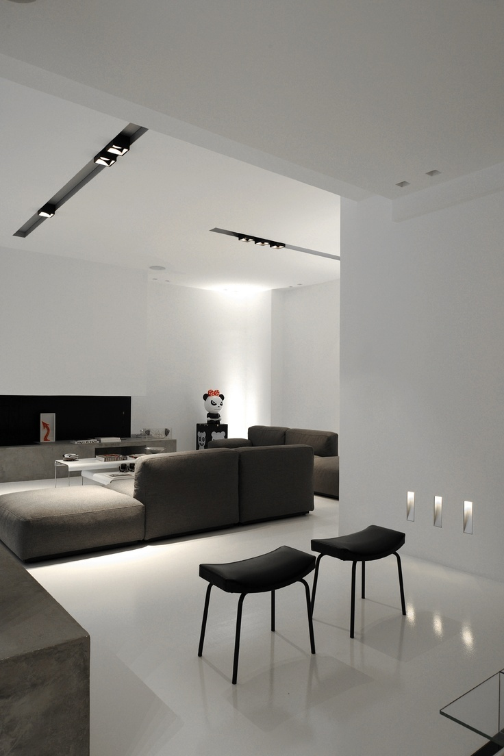 a white minimalist living room with a concrete console, black stools and dark sofas