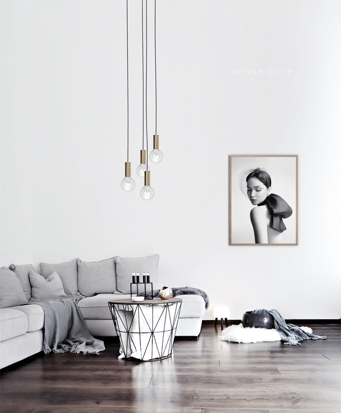 a minimalist living room with a grey sofa, an artwork, a geometric table and pendant lamps