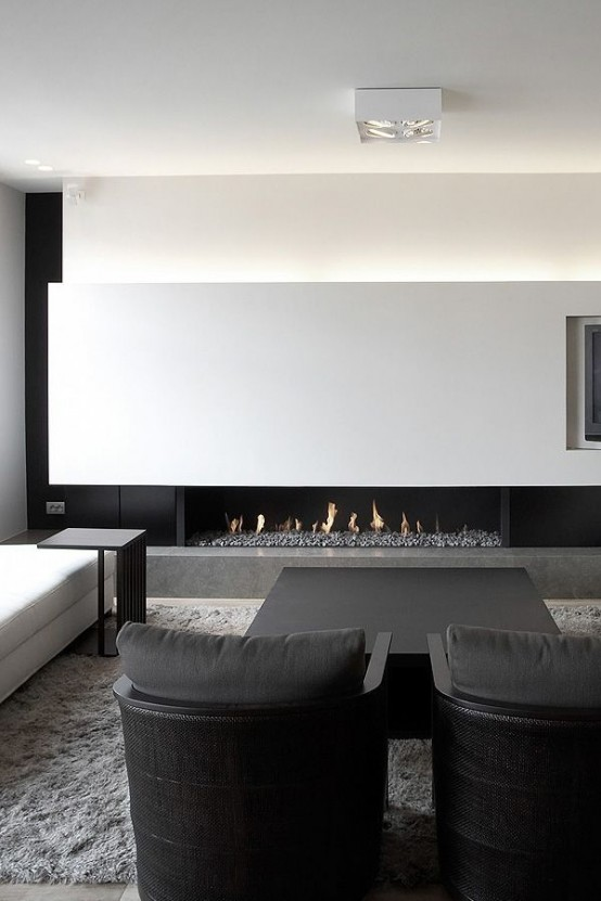 a super elegant black and white minimalist living room with a lit up wall, a fireplace, comfortable black and white furniture