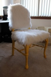a white faux fur chair with refined vintage legs is a stylish piece to use in your space