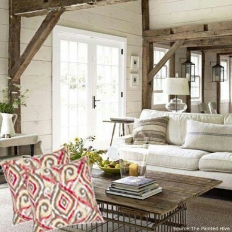 a neutral farmhouse living room with white and wooden furniture, wooden beams and colorful pillows plus greenery