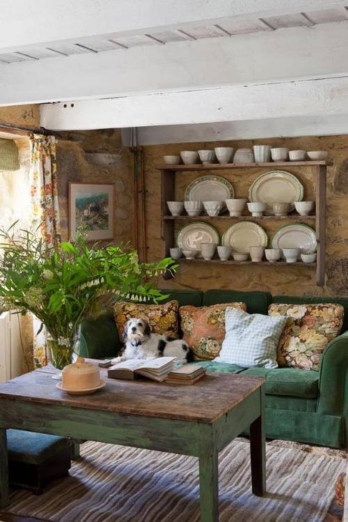 a rustic living room with a green sofa, some shabby chic and rustic furniture and potted greenery