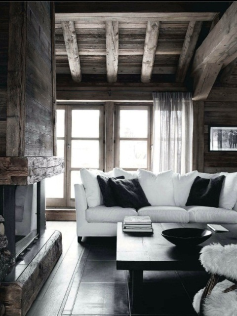 a contemporary meets rustic living room with a hearth, wooden beams on the ceiling and chic black and white furniture