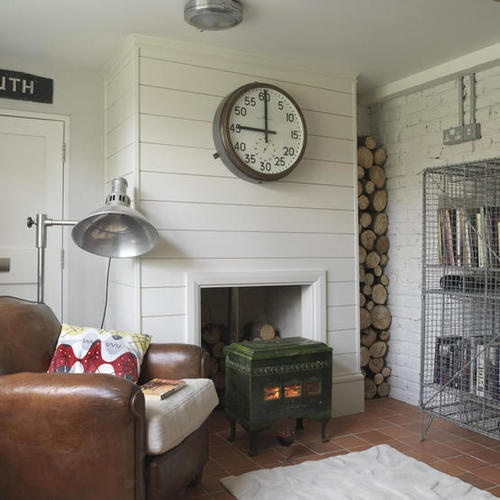 a neutral rustic living room with shiplap on the walls, a hearth and firewood plus some retro furniture