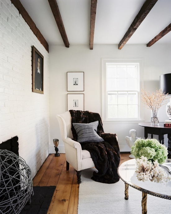 dark wooden beams, a fireplace and white brick walls give a more rustic and less formal look to the space