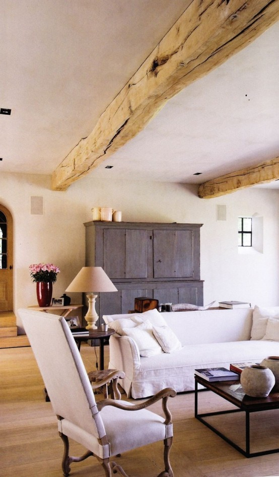 wooden beams on the ceiling and a buffet of reclaimed wood make this living room feel rustic
