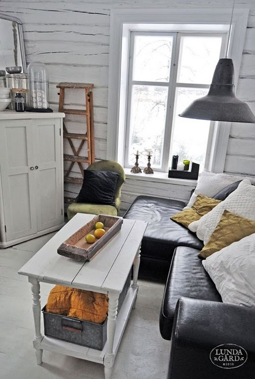 a rustic Nordic space with whitewashed wooden walls, retro furniture and a metal lamp over it