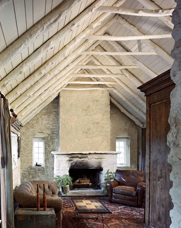 an attic ceiling with beams, a hearth and stone walls make up a cozy rustic backdrop for filling the room