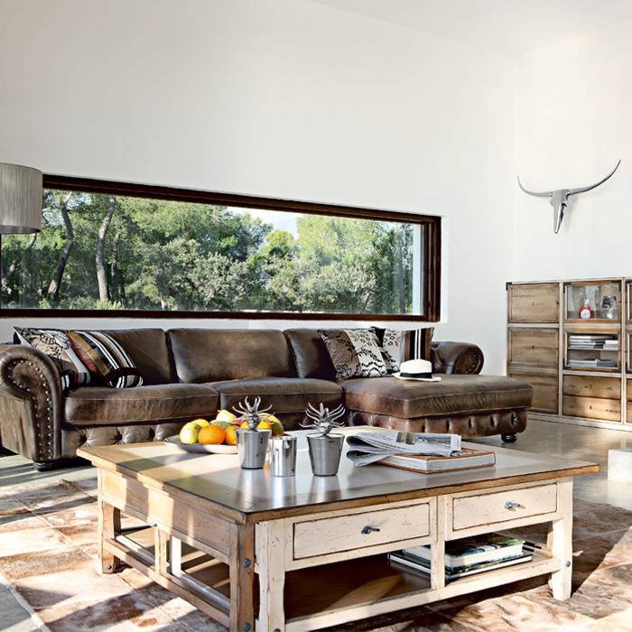 a modern meets rustic space with wooden and leather furniture, a skull, colorful pillows and much light