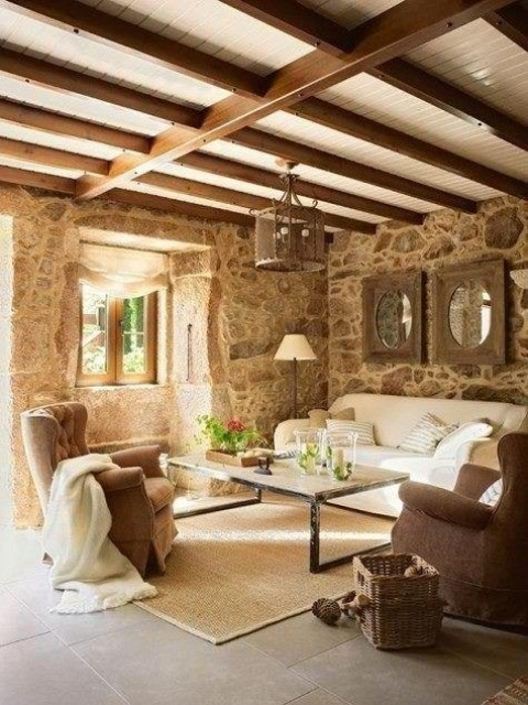 a Provence-style living room with wooden beams and stone walls plus elegant vintage-inspired furniture