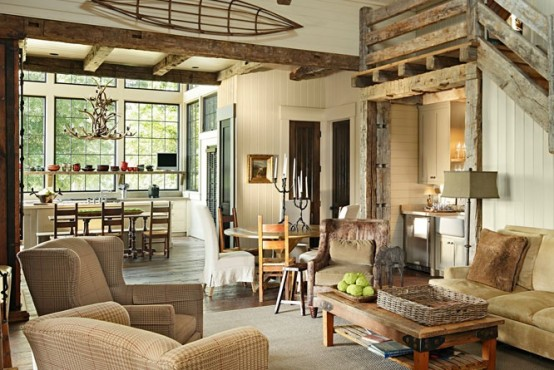 a rustic living room done with shiplap and reclaimed wood, wooden beams and a wooden staircase plus retro furniture