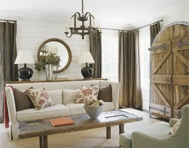 a rustic meets modern living room with wooden doors, shiplap on the wall and a reclaimed wooden coffee table