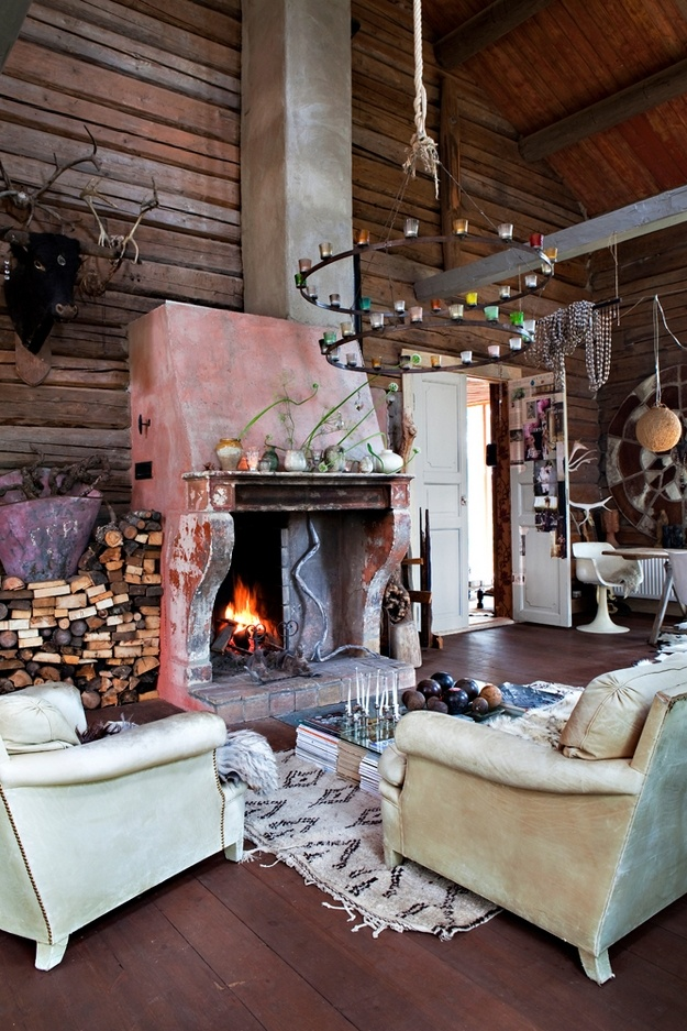 an eclectic living room with cabin touches   much wood, a large fireplace and a firewood storage