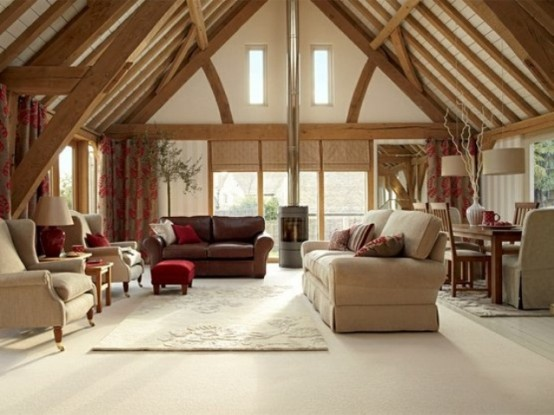 an attic ceiling with beams and a hearth make this open plan living room very cozy and welcoming