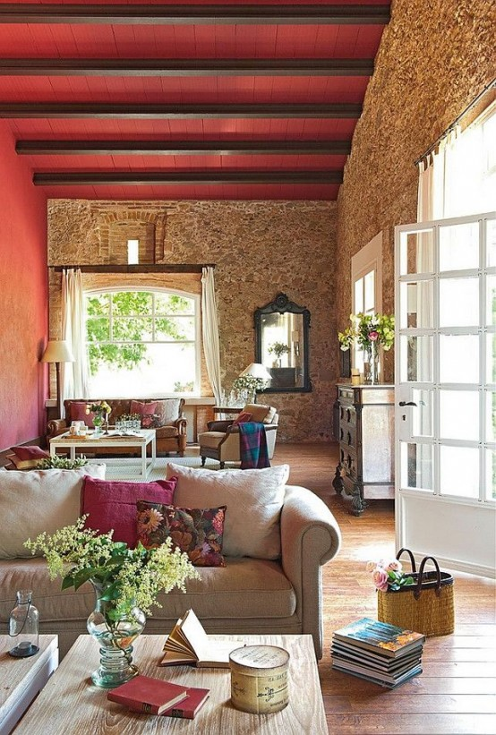 a Provence living room with stone walls, bright red touches, vintage furniture and large windows