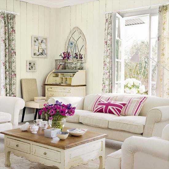 a neutral rustic living room with shiplap on the walls, vintage furniture and floral curtains