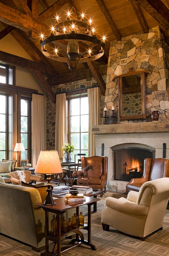 a cabin living room with a stone clad fireplace, a large chandelier, some leather furniture
