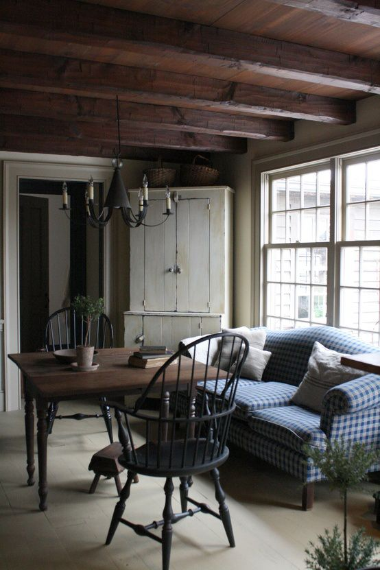 a rustic living room with wooden beams on the ceiling, a wooden dining set, cozy farmhouse furniture