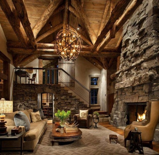 a rustic cabin living room with a fireplace clad with stone, a stone staircase and a large orb chandelier of wood