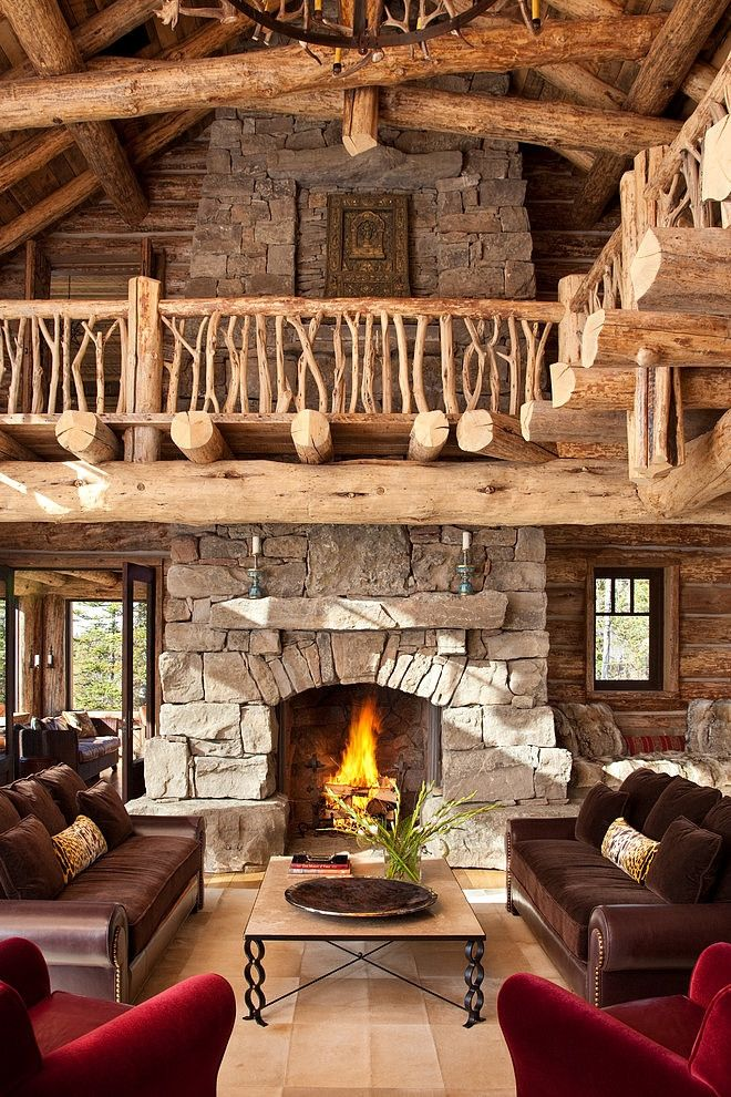 a cabin living room with a stone fireplace, a wooden staircase with beams, elegant furniture