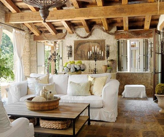 a Provence living room with a wooden beam ceiling, stone walls and chic furniture