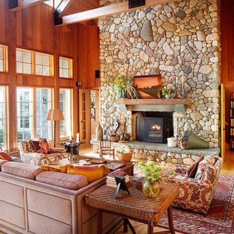 a stone fireplace, wooden walls, bright furniture and potted greenery and much natural light