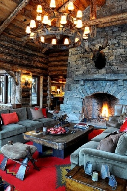 a bright cabin living room with wooden walls and a stone hearth, a reclaimed wooden table and a chandelier