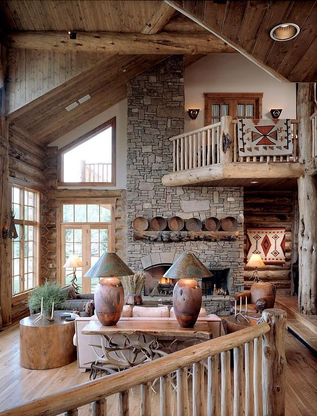 a cozy rustic cabin living room done with plenty of wood and stone, with a fireplace, wooden plates, a tree stump table and cozy furniture