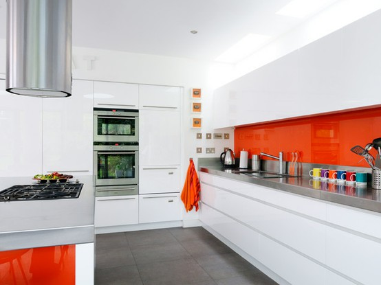 an all-white minimalist kitchen with bold orange touches - a backsplash and sides for a cheerful and fun look