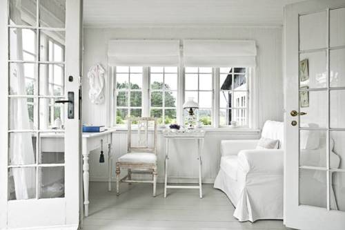 All-white Scandinavian room with a bunch of windows and a glass door.