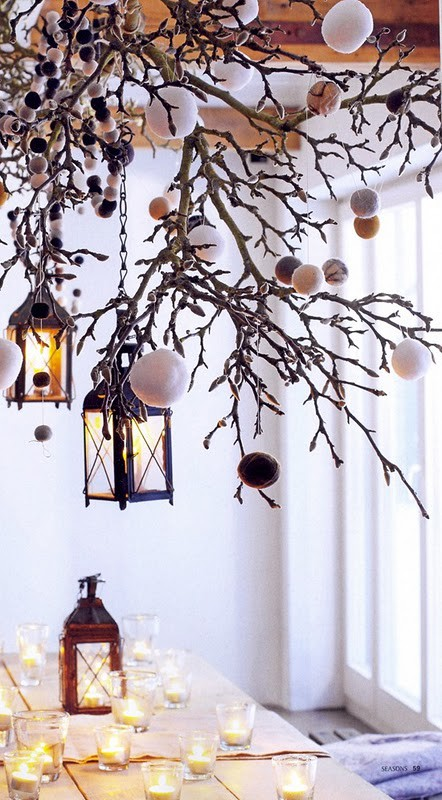 Hang some rustic lanterns on a tree branch and you've got yourself beautiful fall-winter piece of decor. Add some ornaments to it to make it Christmas ready.