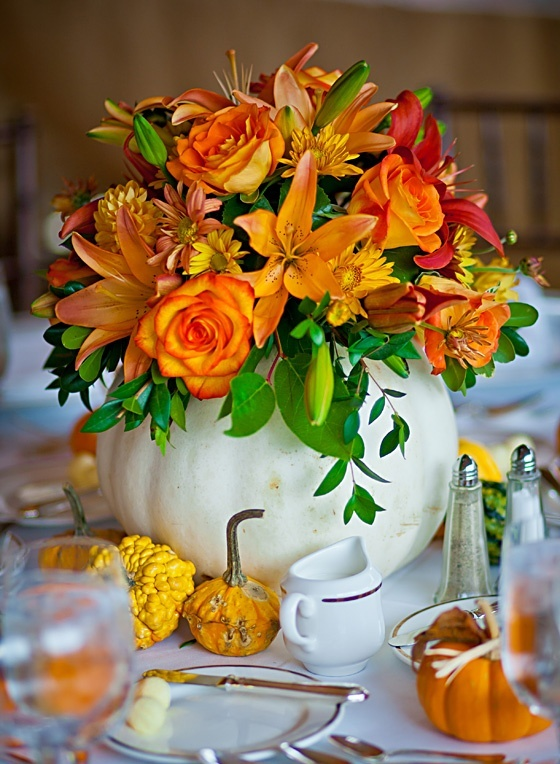 an oversized white pumpkin as a vase with orange and red blooms and greenery is a cool and bold fall centerpiece
