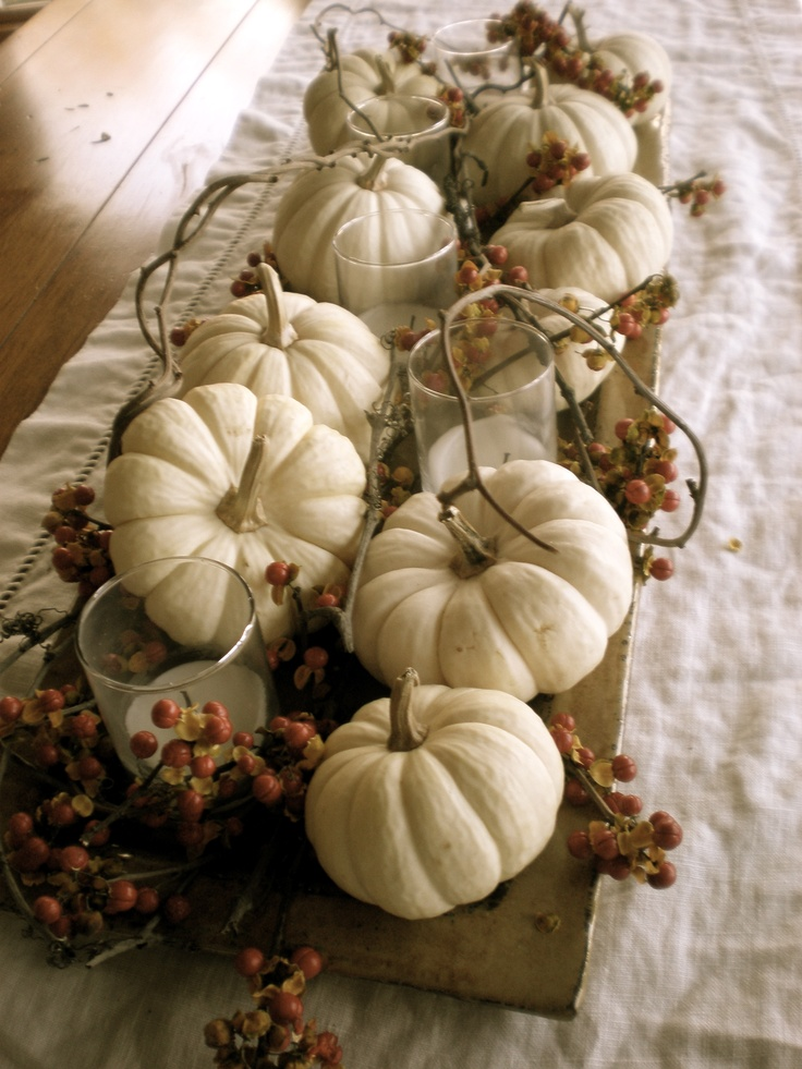 a tray with white pumpkins, berries and pillar candles in glasses is a neutral and peaceful fall centerpiece
