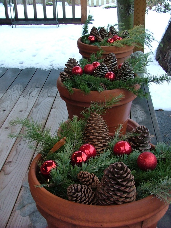 Stuff evergreen trimmings into terracot planters, add some ornaments and pinecones to them. Next, line them up on your porch to add some greenery to it.