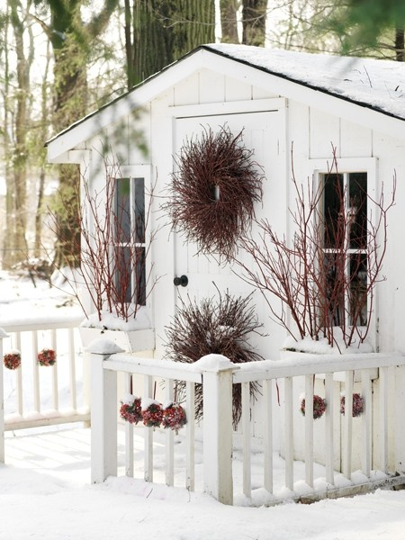 Red ornaments strung along the charming white fence up the festive mood. Besides, two wreaths give this  entryway a fairy-tale feel.