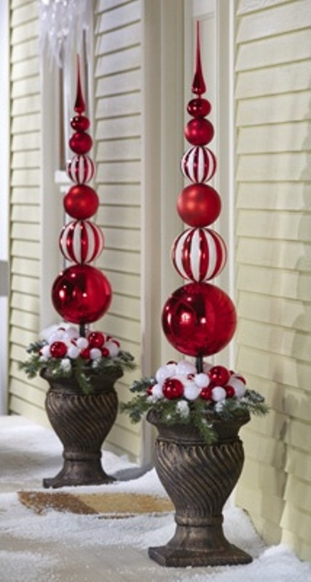 Two urns, filled to the brim with pine twigs and faux topiaries made of Christmas ornaments are perfect for dramatic holiday greeting at the front door.