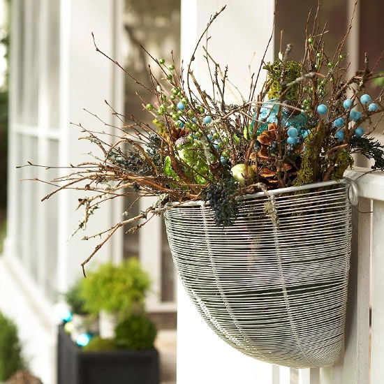 Instead of a wreath, try hanging a basket filled with greens, twigs, pinecones or ornaments.