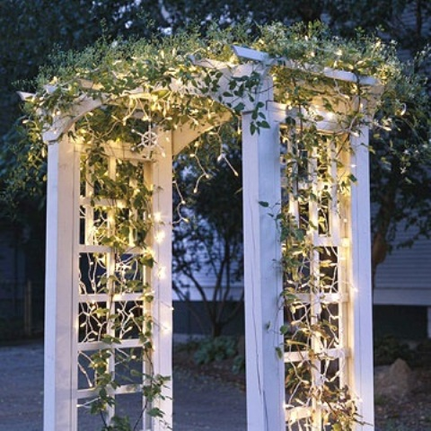 outlining a garden arch in garland with christmas lights is an elegant and simple way to