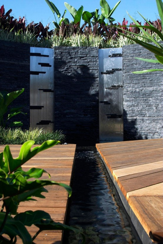Contemporary metal water walls framed in black stone.
