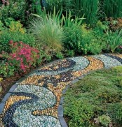 a bright pebble path in yellow, mint green and black with a catchy pattern and dark brick borders