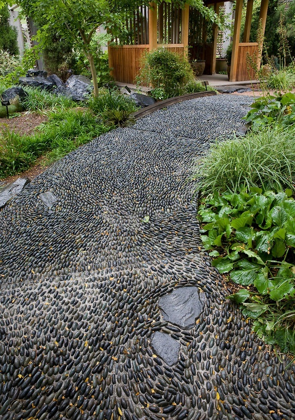 a black pebble garden pathway done with chaotical pattern looks very relaxed and very chic
