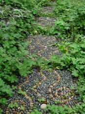 a pebble garden path with black and neutral pebbles with a swirl pattern and curves