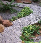 a polished pebble path in grey is a chic idea that will match most of garden styles and decor