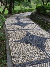 a very bold and eye-catchy neutral and grey pebble pathway with creative patterns and brick lining up